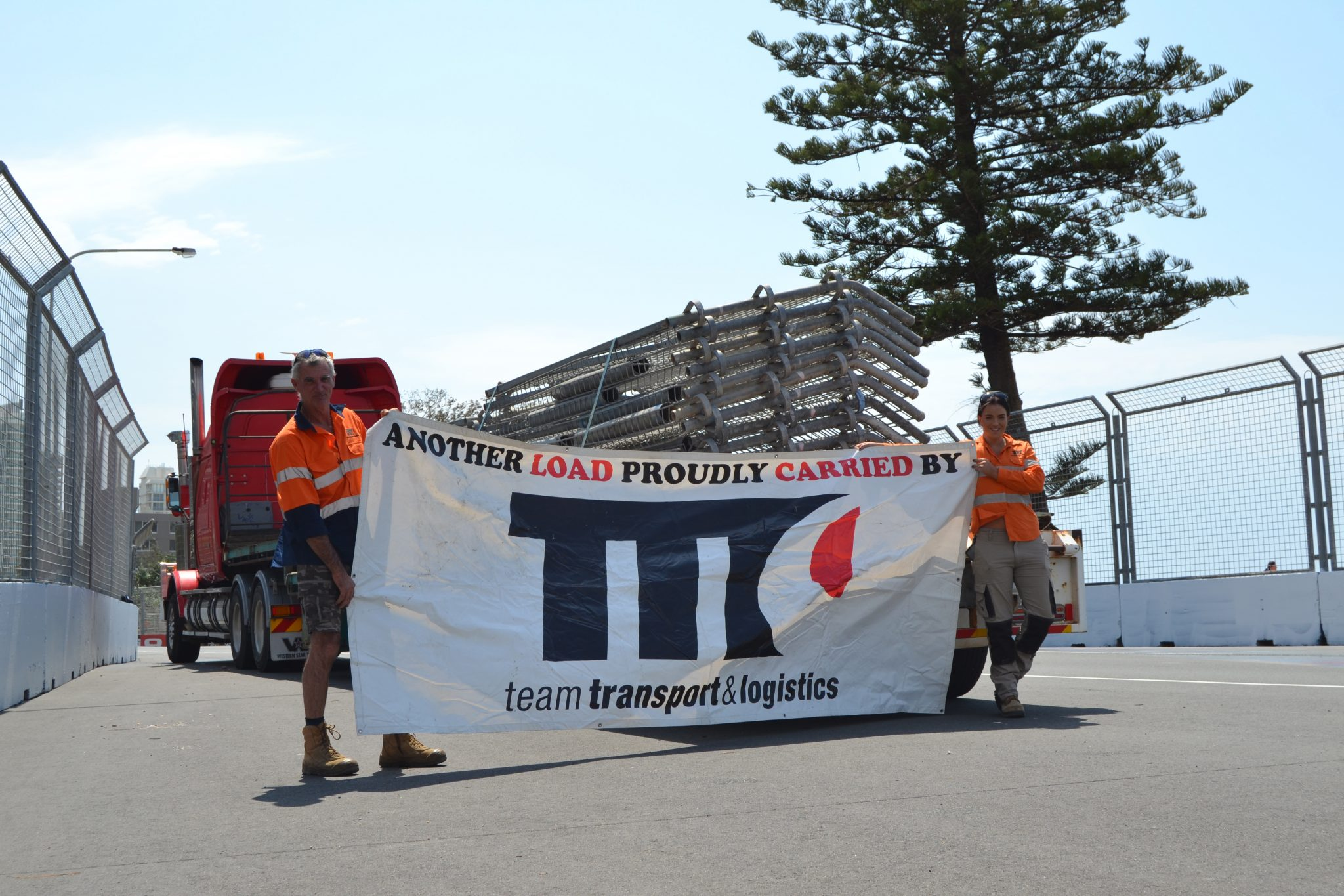 Team transport and logistics staff holding banner on the road