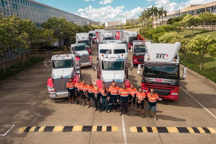 Team transport staff posing for a picture with team transport vehicles in the background
